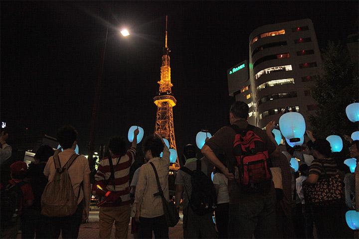 桜通久屋西交差点でテレビ塔に向かって提灯を掲げる参加者ら