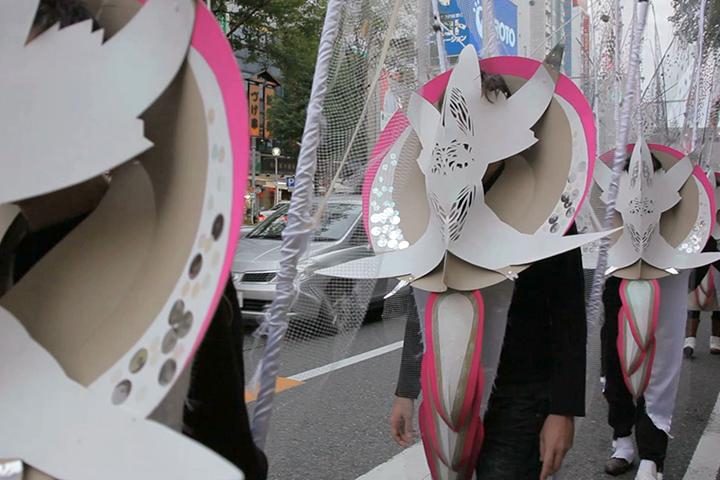 顔を覆う白いマスクと2本の羽のコスチューム.マーロン・グリフィス《太陽のうた》