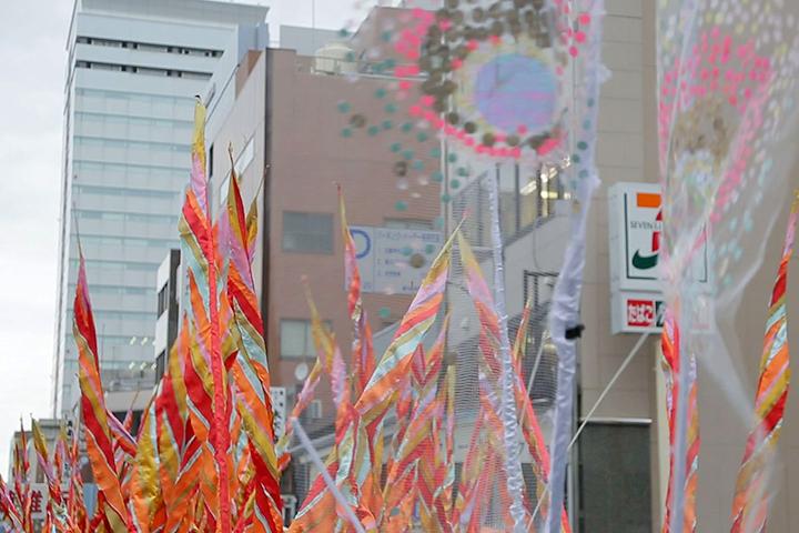 カラフルな幟旗とビル.マーロン・グリフィス《太陽のうた》