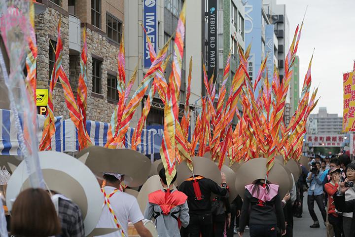 沿道のたくさんの人が見守る中パレードが進んだ.マーロン・グリフィス《太陽のうた》