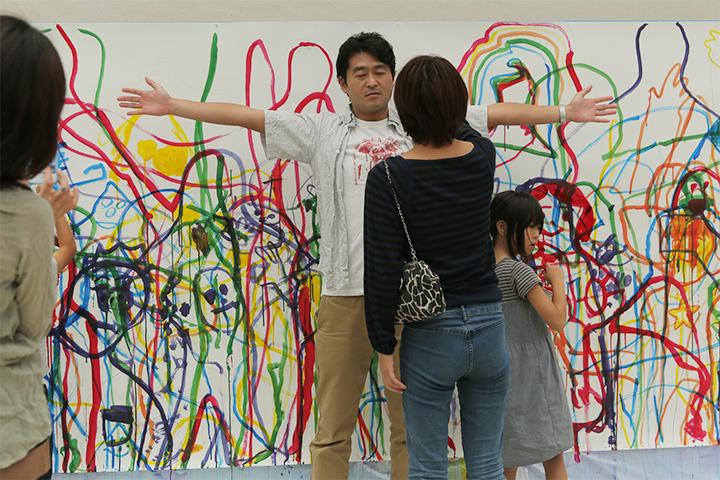 ポーズをとるお父さんと鉛筆で輪郭を描くお母さん
