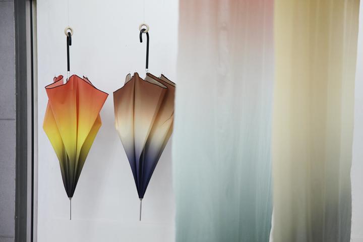カラフルなグラデーションを使った傘や布を展示