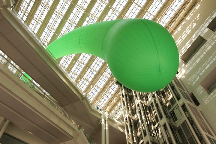 松井紫朗の作品. 緑色の巨大バルーンが芸術文化センター10階からぶら下がる