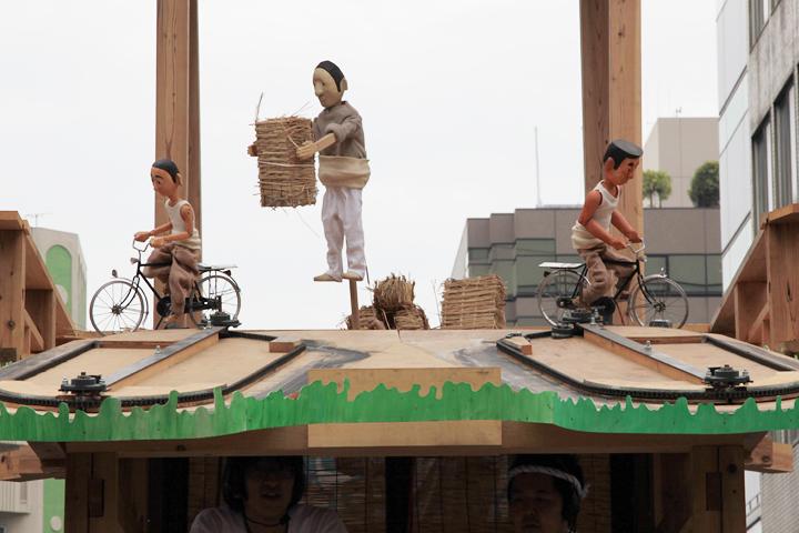 山車の上でからくり人形を上演. 自転車の荷台に荷物をのせる