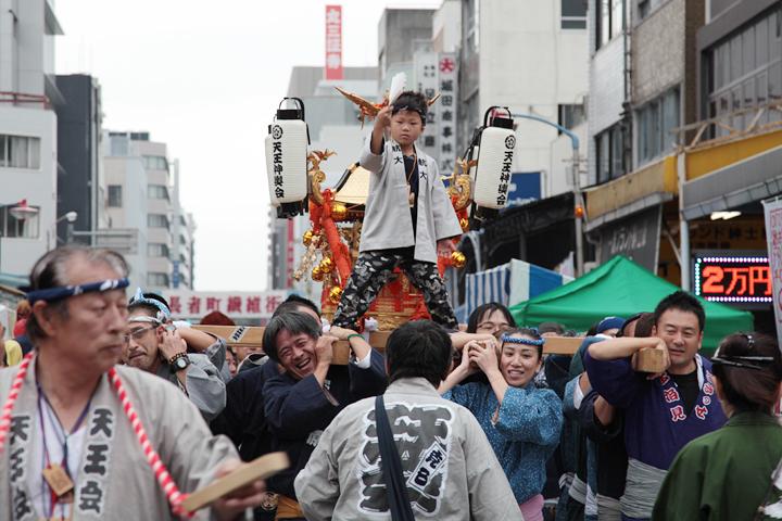 凛々しい姿で神輿に立つ少年