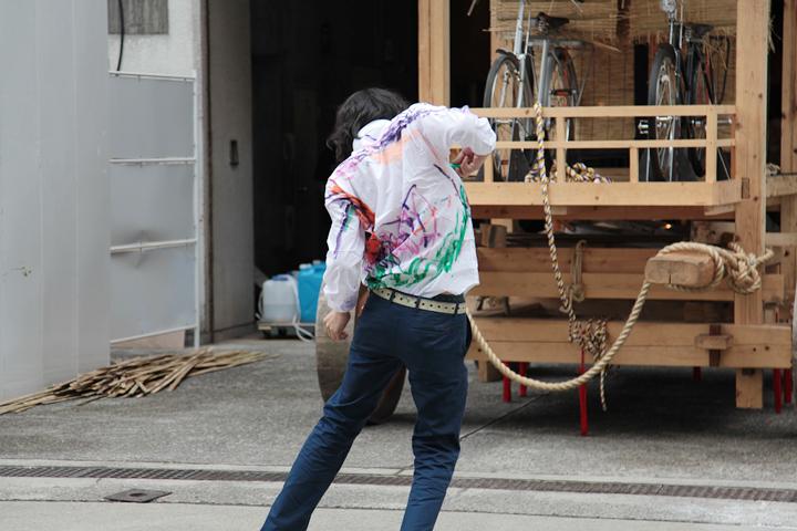 村田峰紀のパフォーマンス. 白いシャツにカラフルな線が引かれていく
