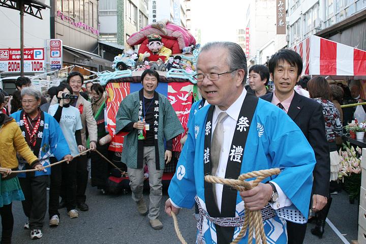 2009年長者町ゑびす祭での「やわらかい山車」曳き回し。写真右から著者、やわらかい山車を曳く神田真秋知事(当時)、山車の前がKOSUGE1-16の土谷享さん