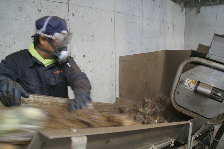 粉砕された生ゴミがベルトコンベアで運ばれていく