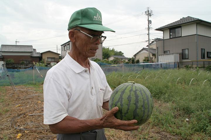 「とよあけEco堆肥」で作ったスイカと生産者のひじ方勝さん(「ひじ」の字は「土」の字の横棒の間、真中縦棒の右側に点がつきます)