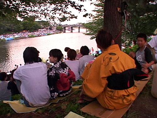 川岸で打上げを待つ観客