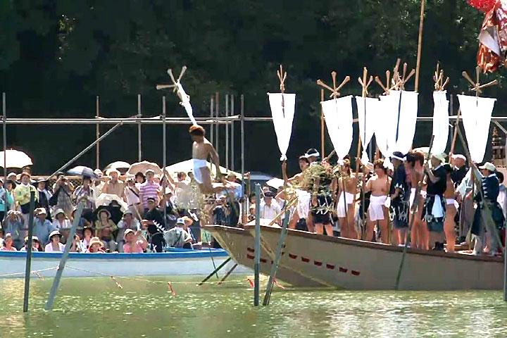 布鉾を持った10人の若者が一人ずつ池に飛び込む