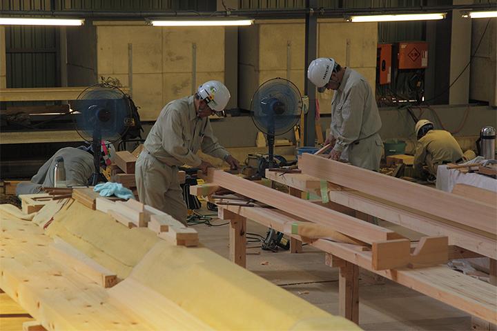 材木を加工する職人ら