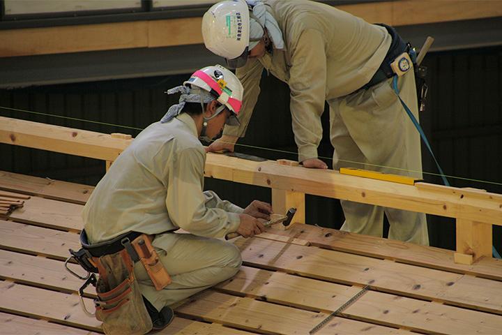 中之口部屋の屋根で作業する職人ら