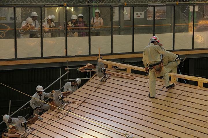 中之口部屋の屋根工事を見つめる見学者ら