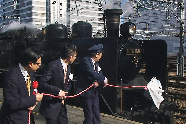 16日、実験走行前の出発式でヘッドマーク除幕を行う川村市長ら