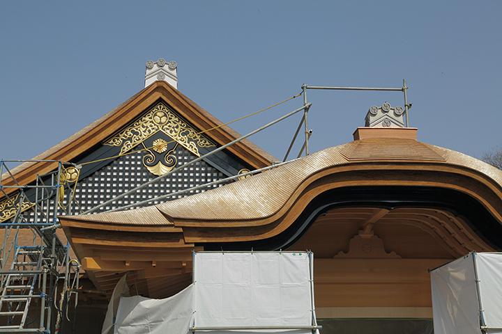 日差しを受けて輝くこけら葺きの屋根