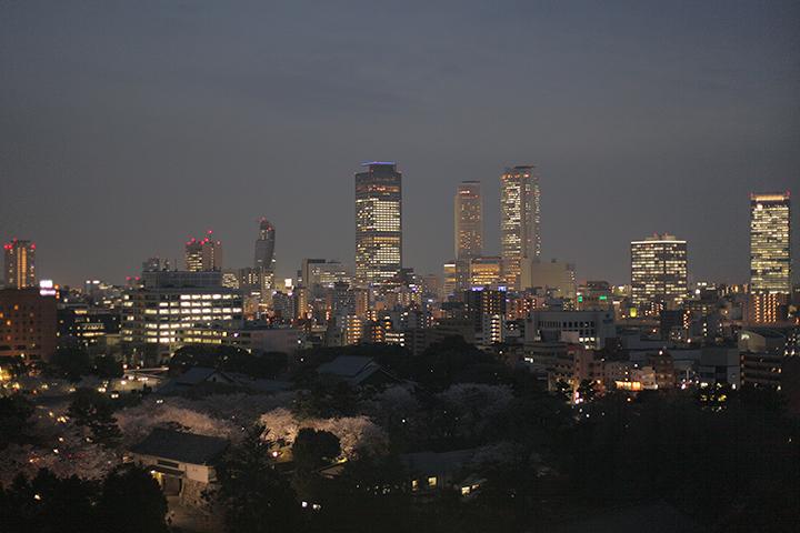 名古屋城天守閣から見た名古屋駅前ビル群と桜がライトアップされた名古屋城正門付近