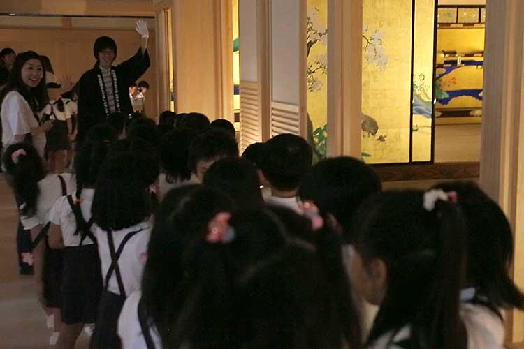 園児に説明する学生おもてなしボランティアメンバー