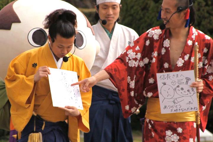 はち丸が描いた色紙につっこむ信長(右)と秀吉(左)