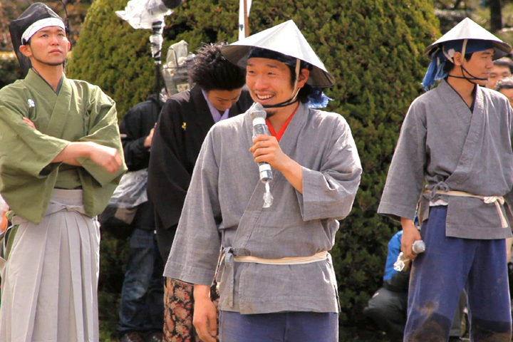 日本一の足軽とお客さんから拍手を受ける市蔵