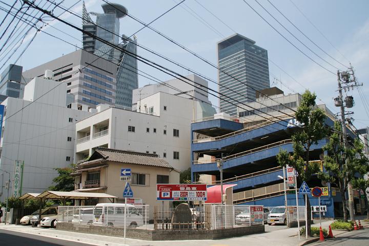 「三四郎」ゆかりの宿の石碑が駐車場(旅館跡)角に立っている