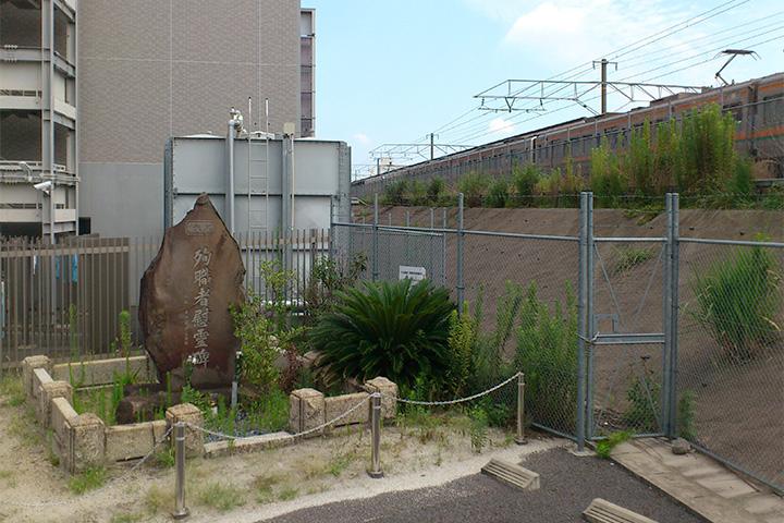 JR大曽根駅南口の駐輪場前にある慰霊碑。慰霊碑の横を電車が走っている